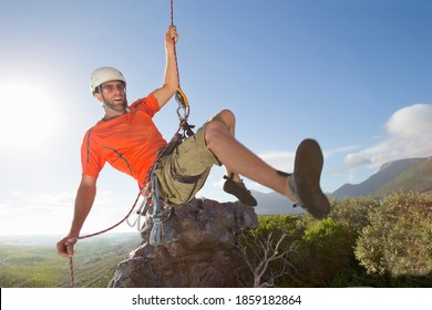 Male rock climber in a helmet holding on to a rope while rappelling down a rock face.