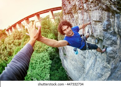 male rock climber. man climbs on a rocky wall, finished climbing and shakes hands with a friend
