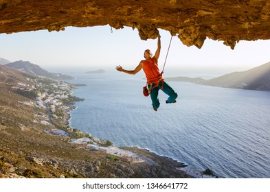 Male rock climber on challenging route going along ceiling in cave