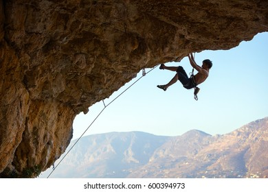 Male rock climber on challenging route on overhanging cliff