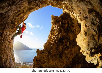 Male rock climber on challenging route in cave