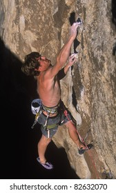 Male rock climber struggles up the edge of a challenging cliff.