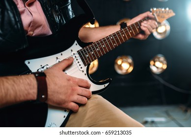 Male rock star with electro guitar on the stage