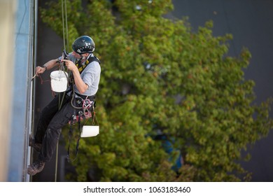 Male rope access industry painter, wearing full safety body harness, a hard hat, working at height, abseiling and using a paint brush painting metal beam, in Sydney city down town CBD, Australia