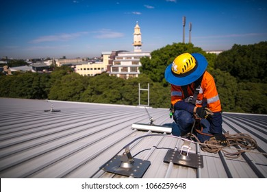 Male rope access industry worker, wearing hard hat working doing inspection services on full arrest anchor point roof safety line  on construction building site, high rise building in Sydney city, OZ