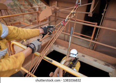 Male rope access industry worker hand wearing hand safety glove protection, while using mechanical advantage three two one pulley system lift the casualty up from confined space manhole construction