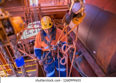 Male rope access miner inspector maintenance fitter worker wearing full safety body harness helmet, using descender abseiling down to work location construction mine site, Perth, Australia