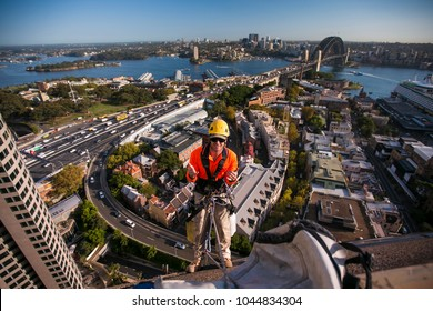 Male rope access windows cleaner wearing  hard hat, long sleeve shirt safety harness, carrying white bucket, working, at height, abseiling down from the high rise building a, Sydney city, Australia