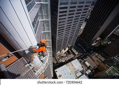 Male rope access windows cleaning wearing long sleeve shirt, safety harness hardhat carrying bucket of water mob, squeegee and ascending cleaning glass windows construction site Sydney , Australia
