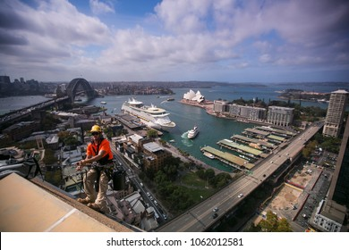 Male rope access worker wearing t-shirt  using static twin rope, working, abseiling off on high rise building construction site near the rock view of Sydney harbour back ground, Sydney, Australia