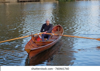 male rower on thames wearing beanie hat in a skiff boat