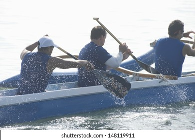 Male rowers paddling outrigger canoe in race