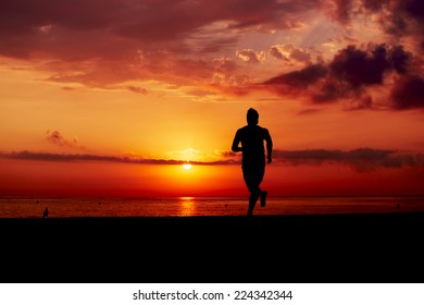 Male runner with athletic figure running alone at orange sunrise on the beach, fitness training on the beach, beautiful runner silhouette in action, fitness and healthy lifestyle