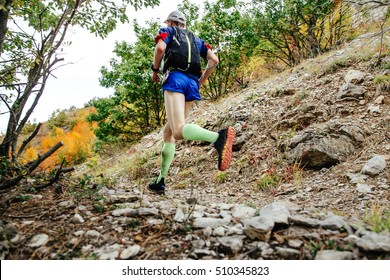 male runner in compression socks running on a mountain trail. backpack for running behind his back
