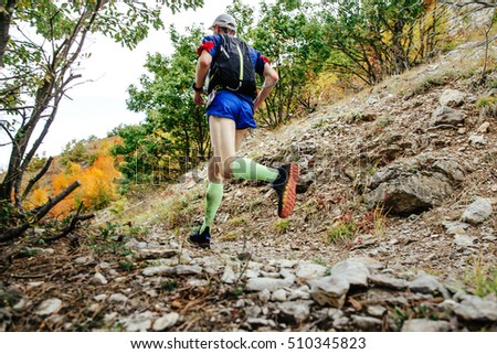 80473ce191 male runner in compression socks running on a mountain trail. backpack for  running behind his