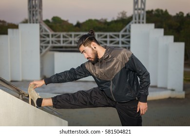 Male runner doing stretching exercise.