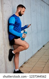 Male runner leaning on wall and using smart phone. In other hand bottle with water.