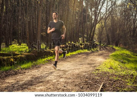 Male runner on nature road in misty forest full of pleasure warm light.