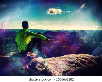 Male runner rest on mountain peak in background hills and clouds.  Abstract filter.