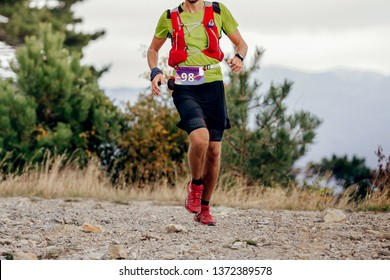 male runner run mountain race with trail vest for running