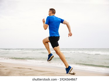 male runner running edge of sea sand beach
