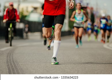 male runner running in front group runners on street of city