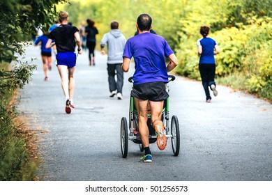 male runner running marathon in autumn city Park with a pram baby