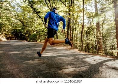 male runner running on forest road in sunlight blurred motion