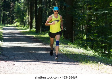 Male runner running on forest road