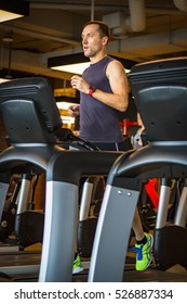Male Runner Running on Treadmill in Health Club