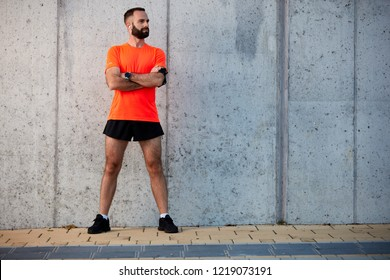 Male runner standing with crossed arms in sportswear outdoors. Healthy lifestyle concept.