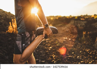 Male runner stretching leg and feet and preparing for running outdoors. Smartwatches or fitness tracker on hand. Beautiful sun light on background. Active and healthy lifestyle concept.