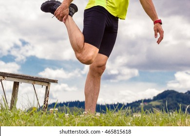 Male runner stretching outdoors at mountains background. Standing quadriceps quad stretch. Walking Heel to Butt.