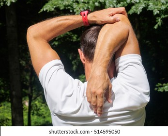 Male runner stretching outdoors. Triceps Stretch.
