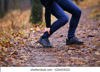 Male runner touching cramped calf at morning jogging. Achilles tendon pain or injury concept background