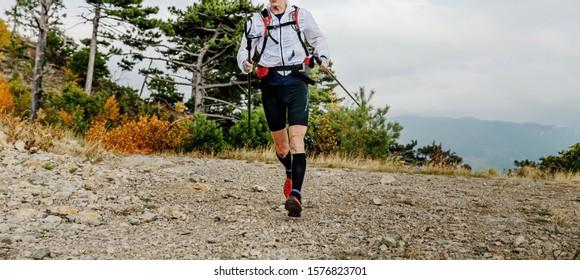 male runner with trekking poles run mountain trail marathon