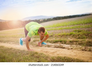 Male runner tripping over and falling down on the cross country trail