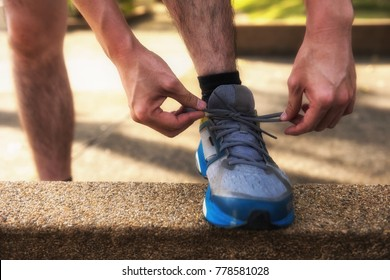 Male Runner tying running shoes or shoelace on footpath with sunset light and getting ready for run. Healthy lifestyle for teenager, middle age worker, and senior people or oldster.
