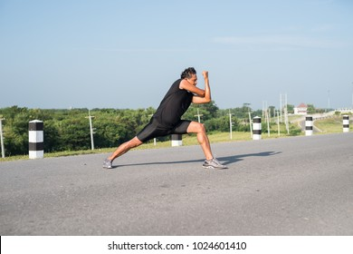 Male runners are stretching the leg muscles to prepare for a run in the morning. The concept of health and fitness