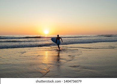 A male running toward the waves with his surfboard under his arm to go surf during the sunset on a beach in Nosara, Costa Rica