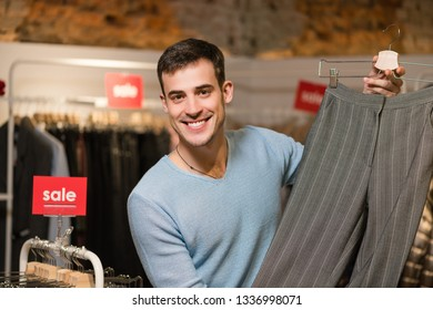 Male sales consultant with female pants in store.
