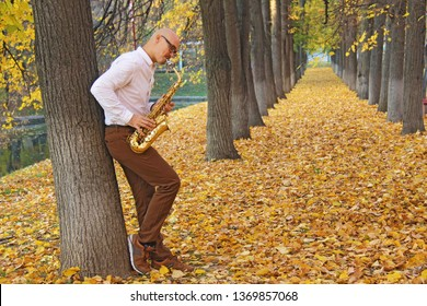 Male saxophonist in white shirt playing the saxophone on the background of the autumn landscape. Romantic saxophone. Saxophone, music instrument played by saxophonist player- Image.