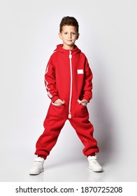 Male schoolboy model showing underside red jumpsuit part for camera standing over studio wall background. Crop shot with fashion clothes detail. Warm trendy attire for winter or autumn advertising