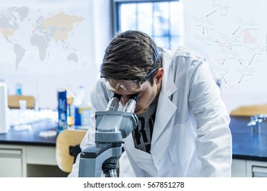 Male scientist looking through a microscope in a laboratory working on some research.