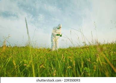 Male scientist in protective uniform analyzing green plants on summer field. Concept of safety and ecology