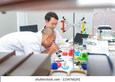 Male scientist standing with techer in lab worker making medical research in modern laboratory. Scientist holding documents folder with analysis results.