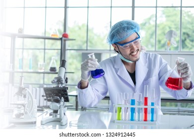 Male scientist testing an experiment in  science lab where there are chemical substances and equipment. He's been analyzing the medicine-related innovation for years now. Successful chemistry concept.