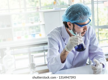 A male scientist testing his experiment in a science lab where there are chemical substances and equipment. Bio technology concept.