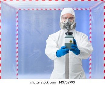 male scientist wearing protection equipment holding a toxic waste container, inside a chamber surounded with red and white tape
