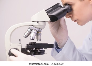 male scientist working in ab with microscope. clinician studying chemical elements in laboratory